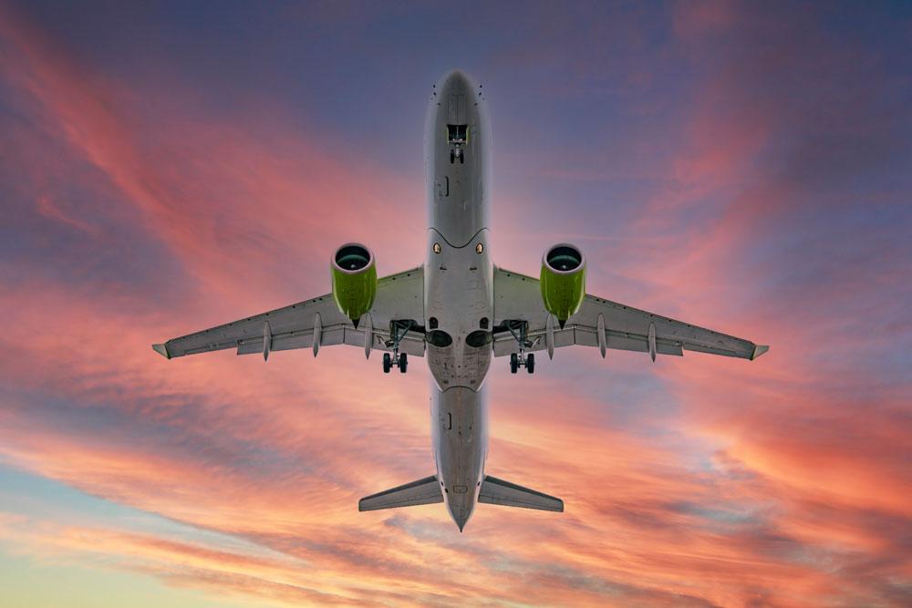 Aeroplane flying overhead at sunset