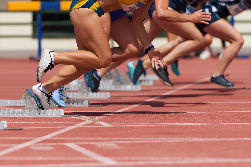 Group of female track runners on starting blocks