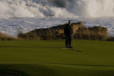 Golfer golfing by the sea
