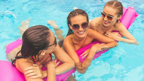 Three beautiful women in pool in summer