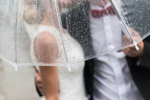 Couple huddled under an umbrella