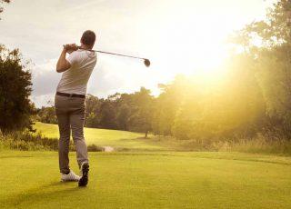 A man swinging a golf club on a course