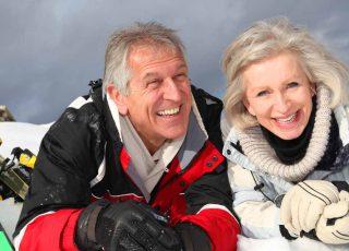 An elderly couple enjoying an active ski life