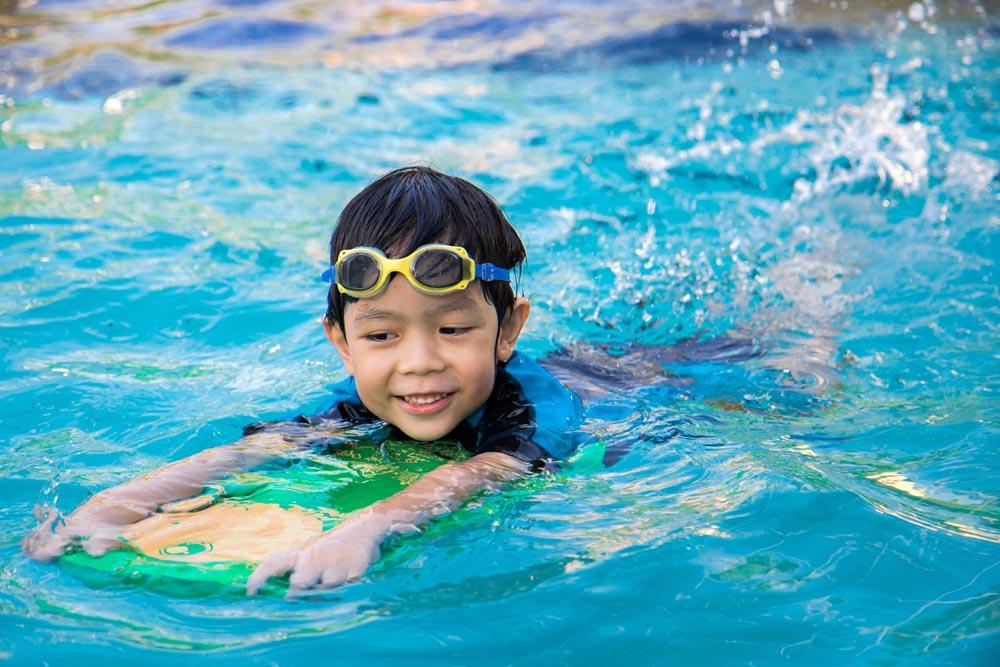 Boy learning to swim in pool