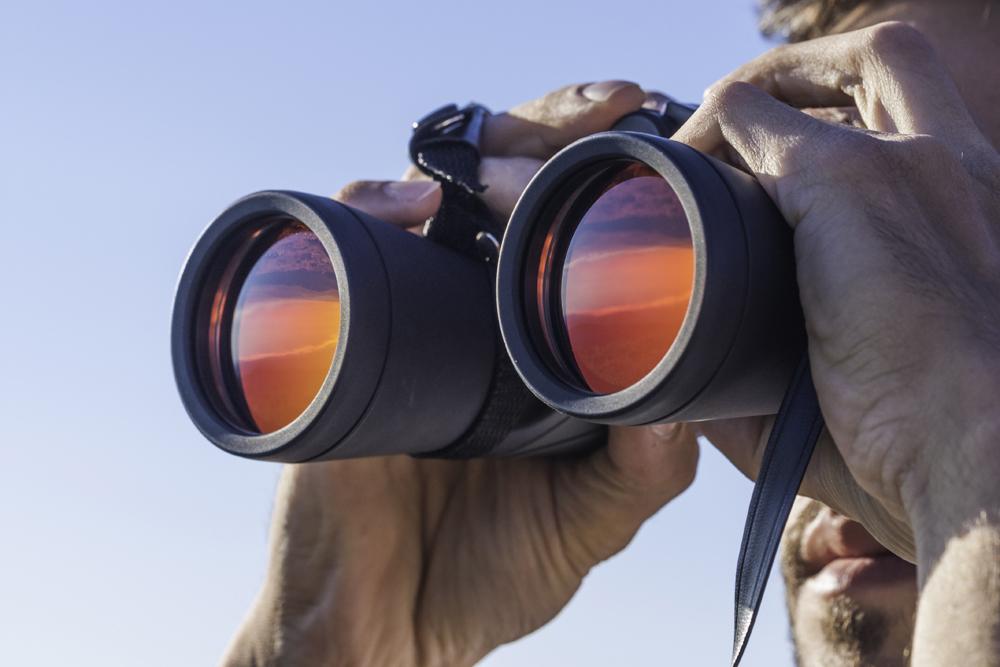 Close up of man looking through binoculars